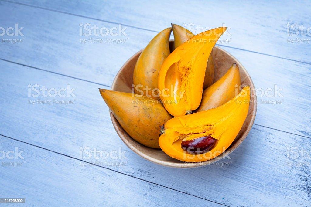 Egg fruit in wooden bowl on wood floor stock photo