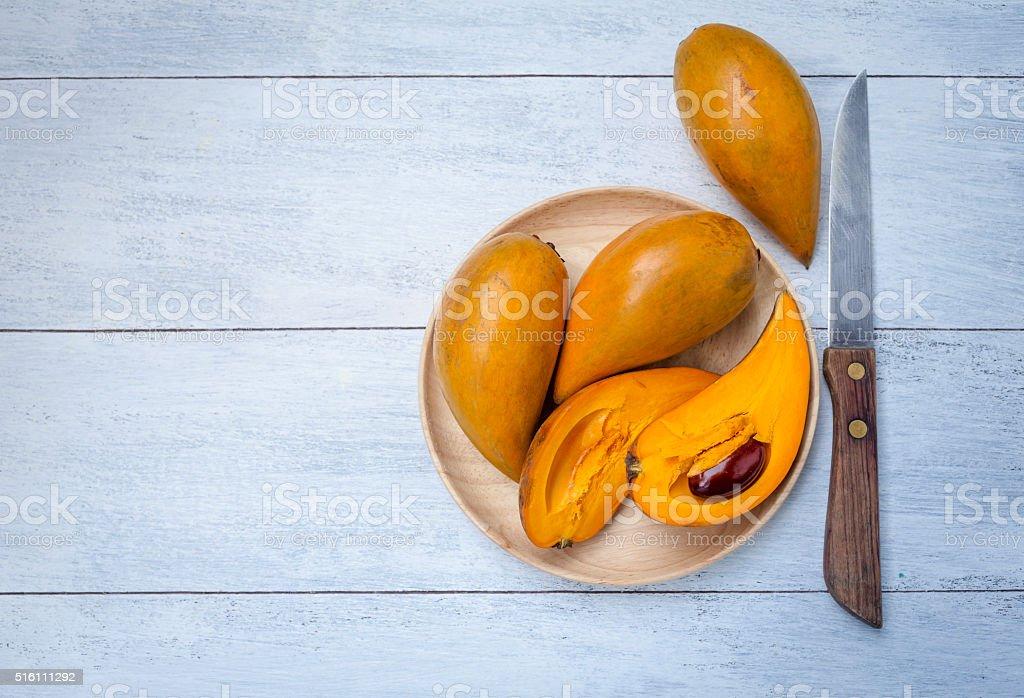 Egg fruit on wooden plate stock photo