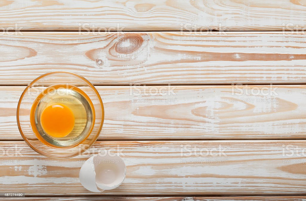 Egg in bowl on board stock photo