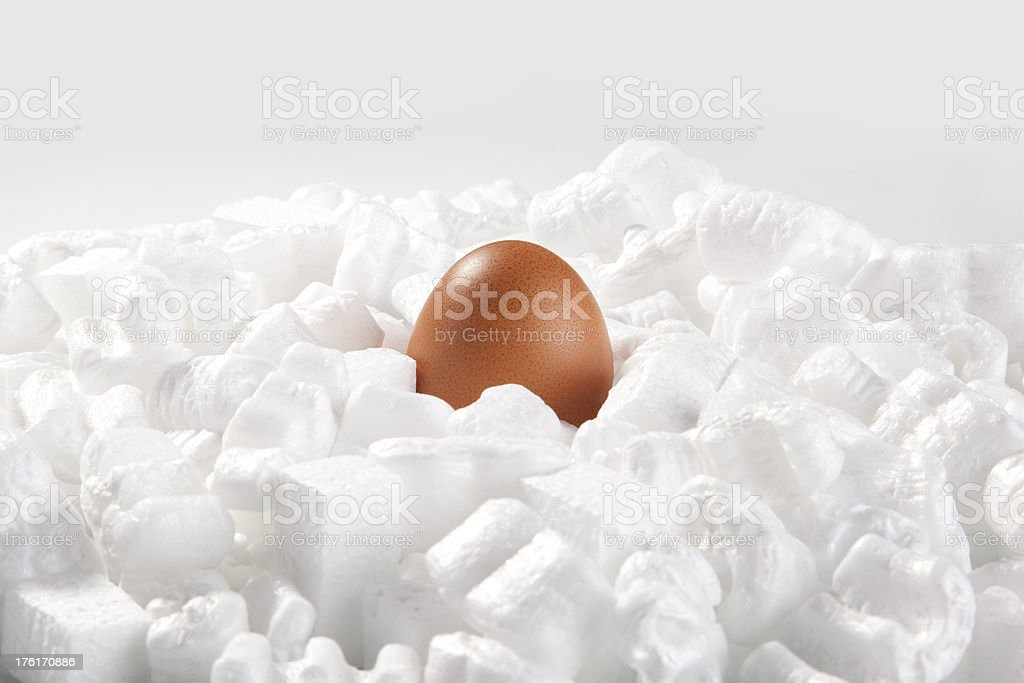 Egg protected by packing peanut stock photo