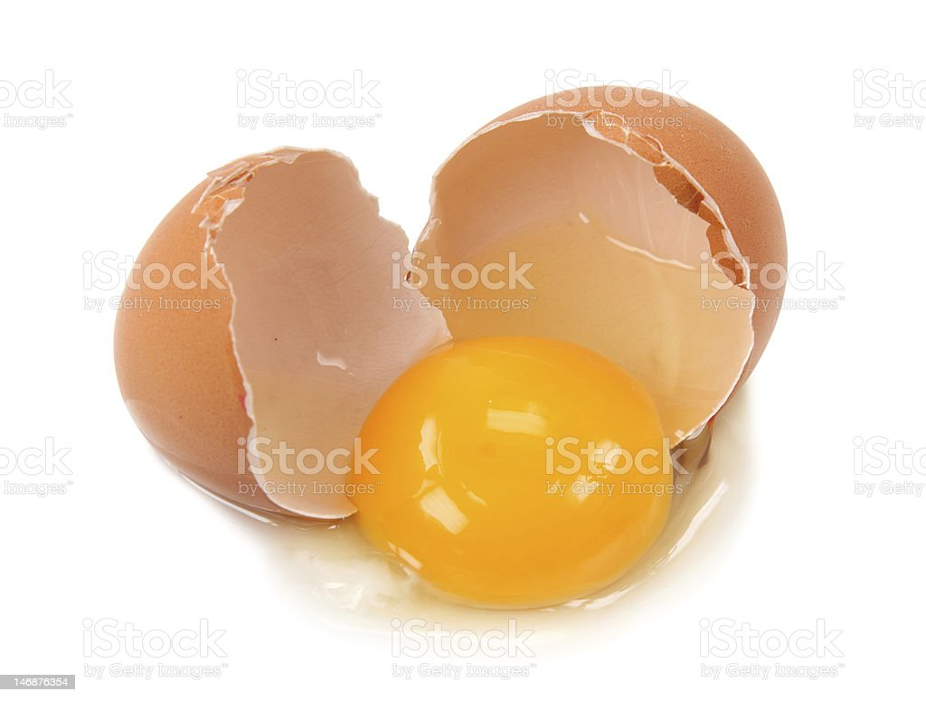 Egg shell broken in middle with yolk and white spilling out stock photo