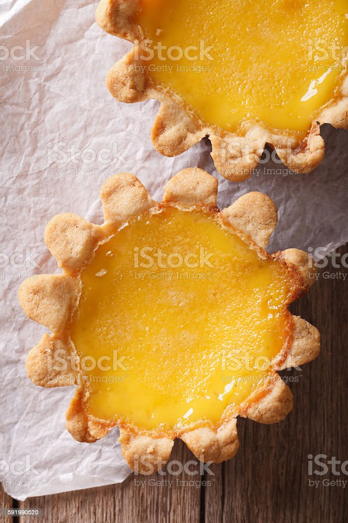 Egg Tart on the paper close-up. vertical top view stock photo