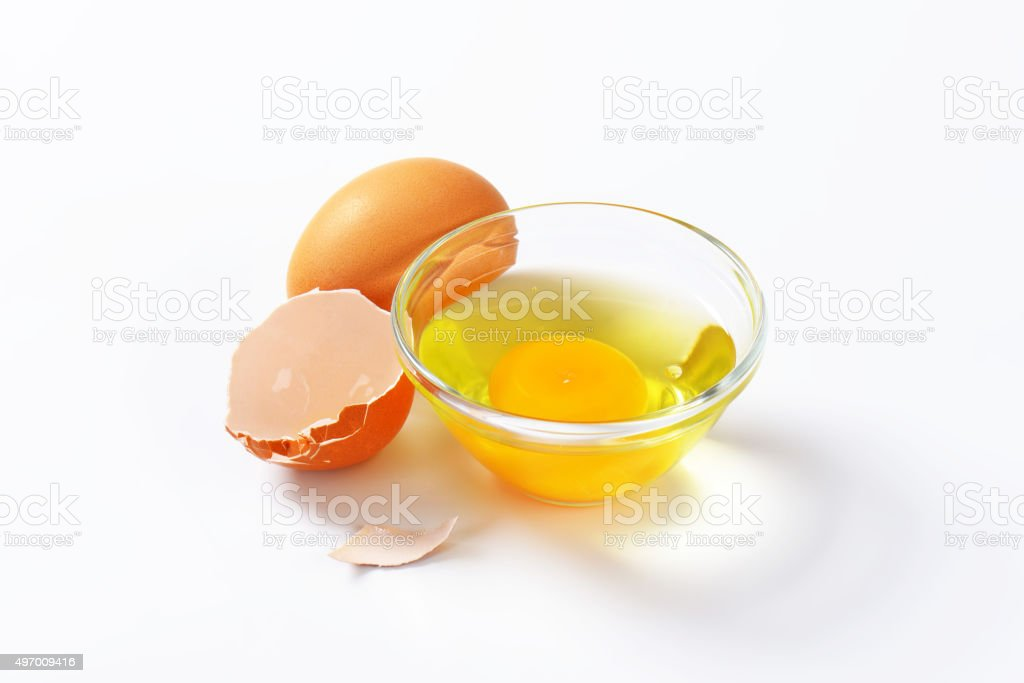 Egg white and yolk in glass bowl stock photo
