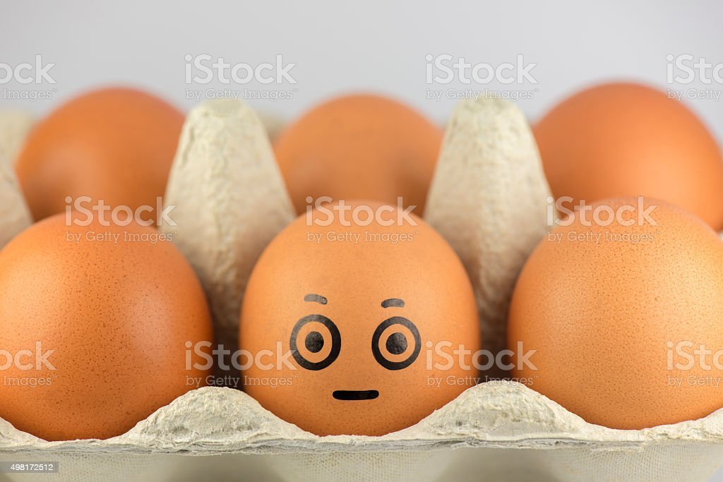 Egg with a face in a egg carton. stock photo