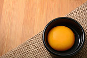 egg yolk in black bowl and on wooden table