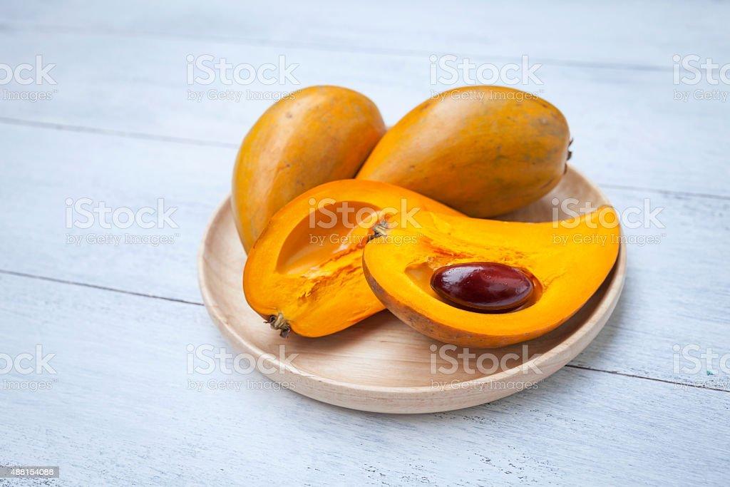 Eggfruit on wooden tray stock photo