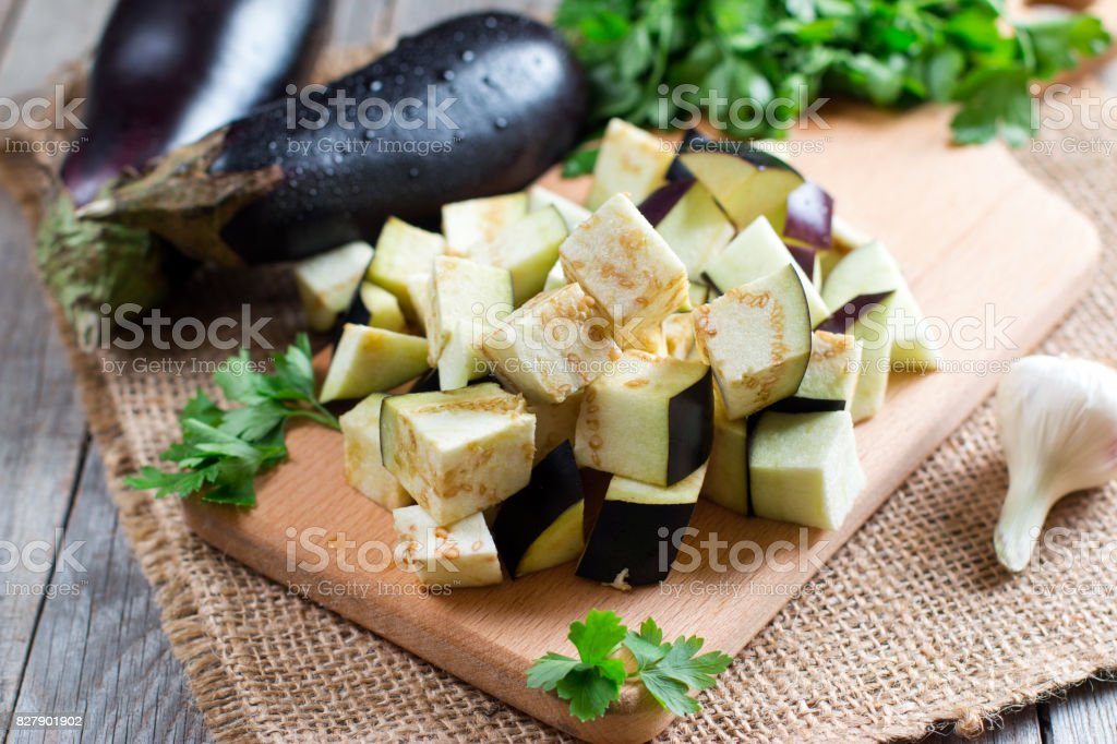 Eggplant cubes on a cutting board stock photo