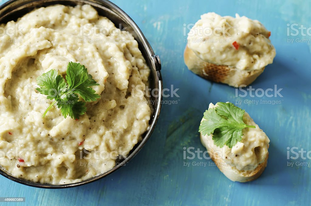 Eggplant dip in bowl and served on bread with fresh herbs stock photo