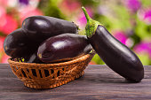 eggplant in a wicker basket on wooden table with blurred
