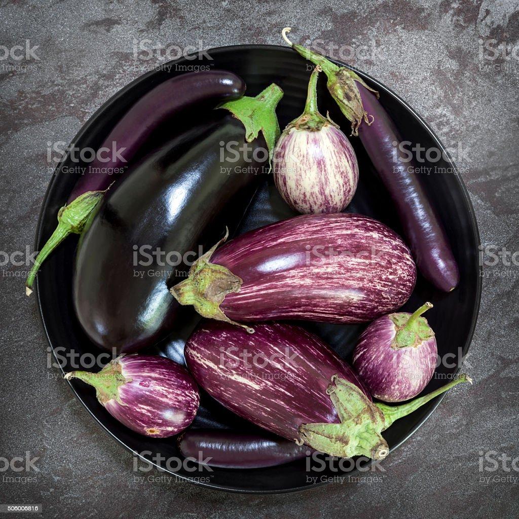 Eggplant Varieties in Black Bowl on Slate Overhead View stock photo