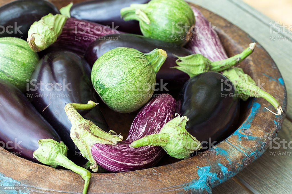 Eggplants and round zucchini on wooden plate stock photo
