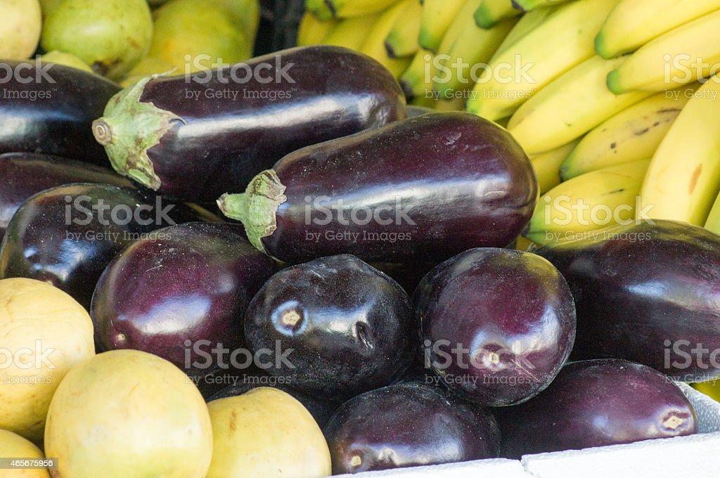 Eggplants or aubergines between bananas and guavas stock photo