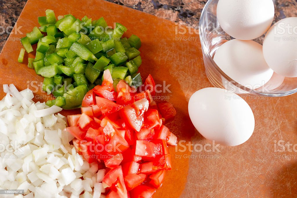 Eggs and colorful vegetables on a kitchen cutting board. stock photo