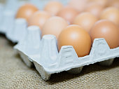 eggs and egg container on brown hemp sack texture background