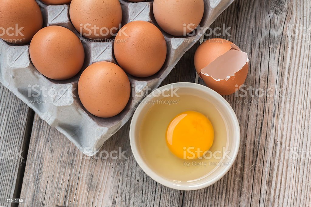 Eggs and Egg yolk in paper tray on wood stock photo