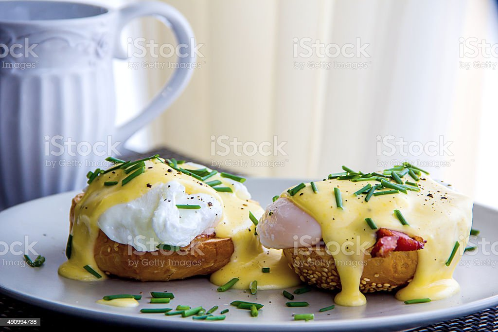 Eggs Benedict and delicious buttery hollandaise sauce stock photo
