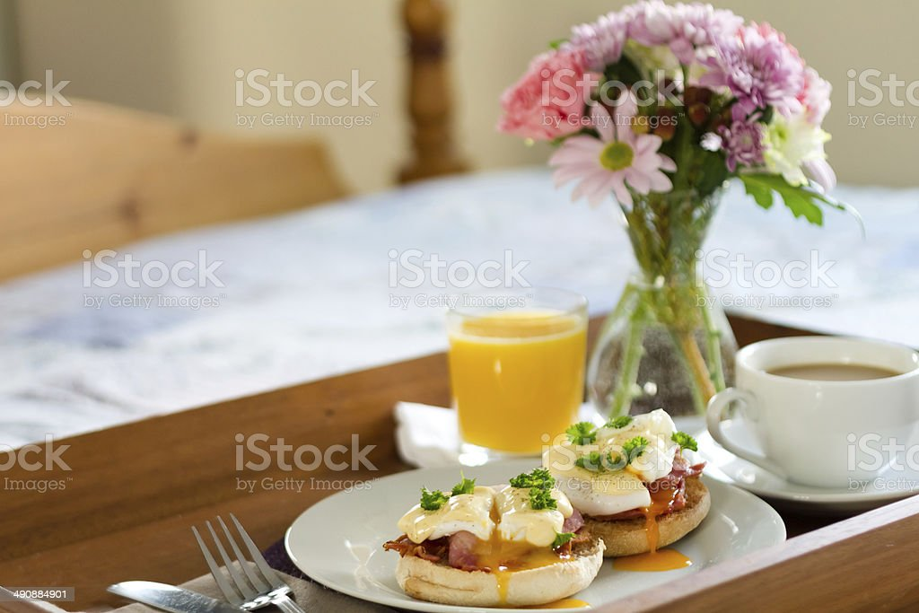 Eggs Benedict on breakfast tray on bed stock photo
