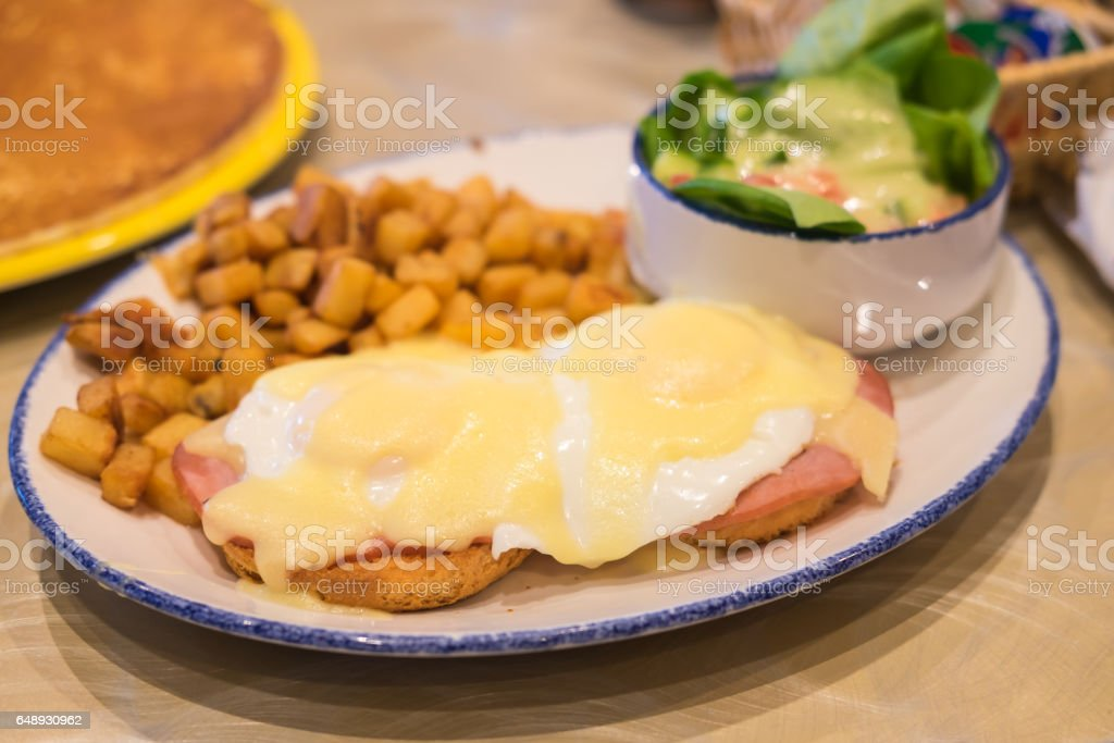 Eggs Benedict with bacon, toast and fresh salad. stock photo