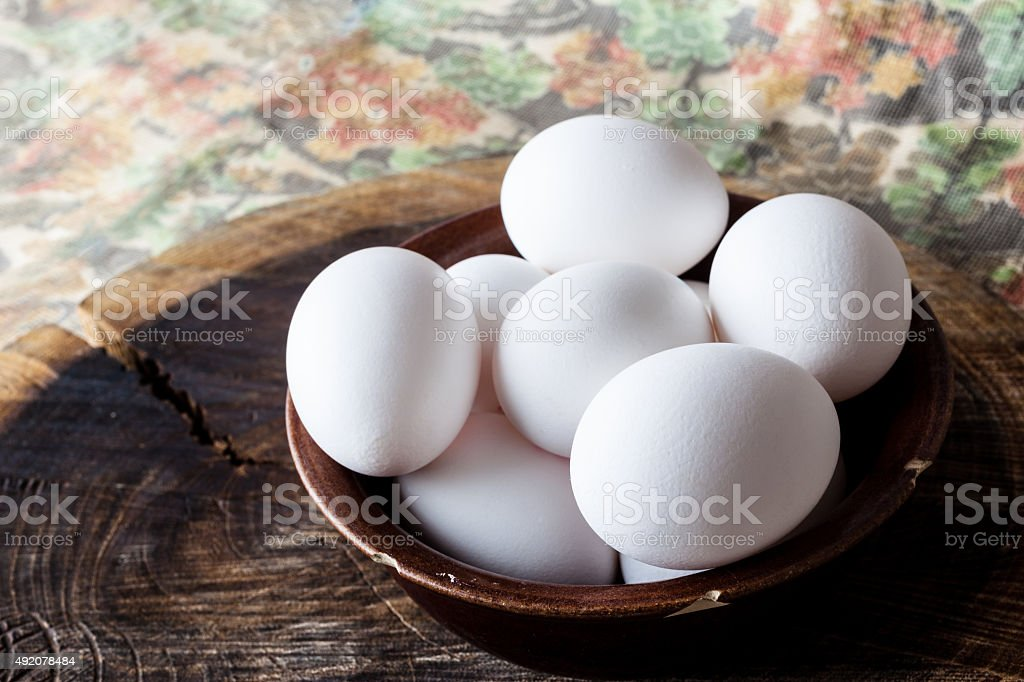 Eggs in a bowl on rural cutting board from side stock photo