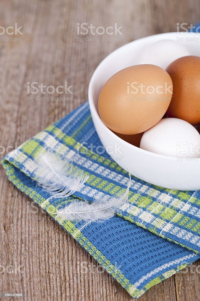 eggs in a bowl, towel and feathers royalty-free stock photo
