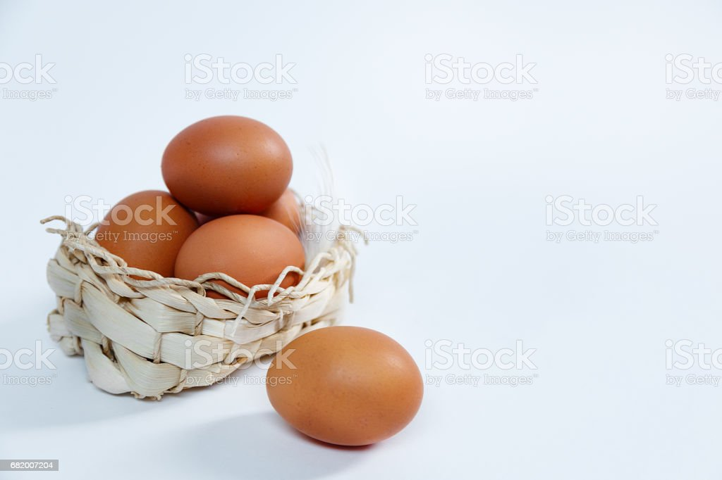 Eggs in a lovely bascket on a white background stock photo