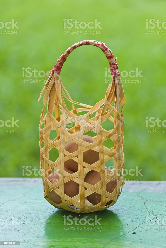 Eggs in basket on the table with green background. royalty-free stock photo