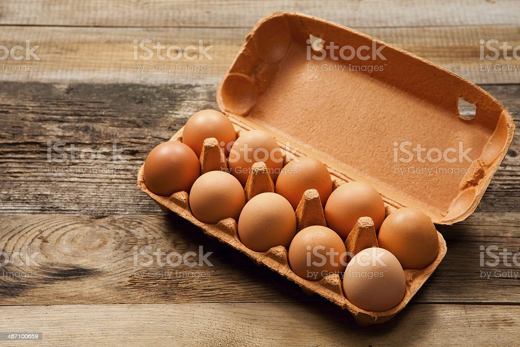 Eggs in the package on wooden table stock photo