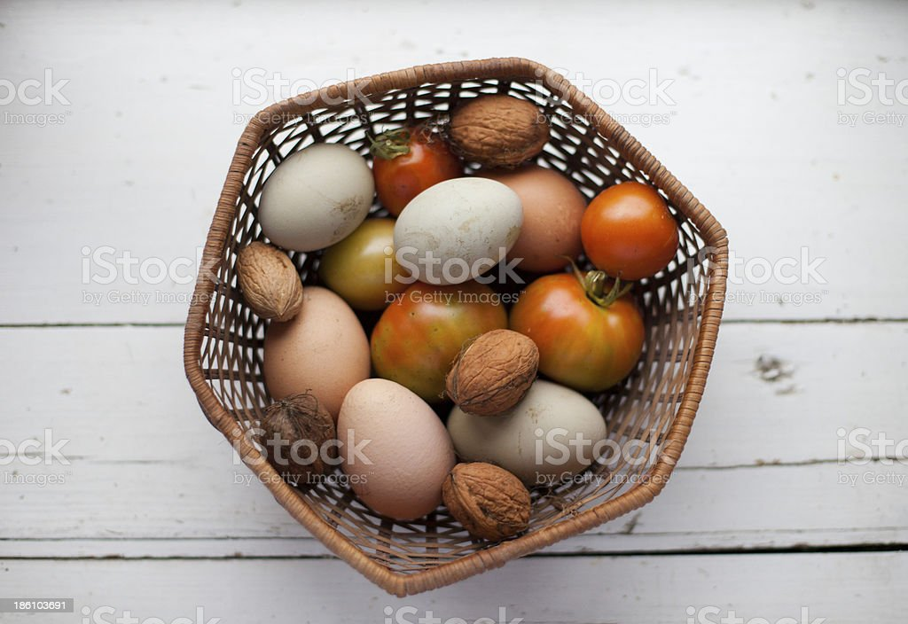 Eggs, walnuts and tomatoes in a basket stock photo