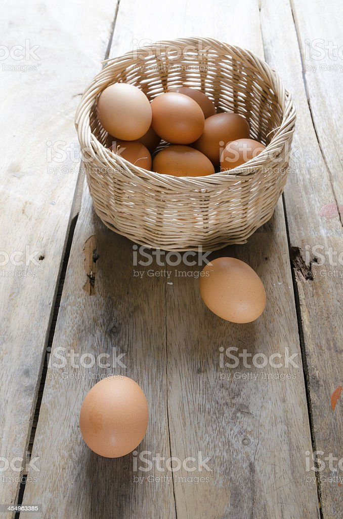 Eggs with basket on wooden floor stock photo