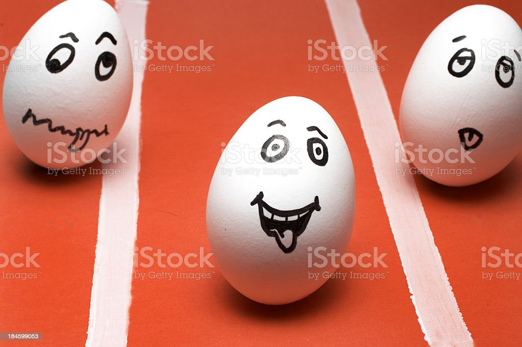 3 eggs with different expressions drawn in on a race field stock photo