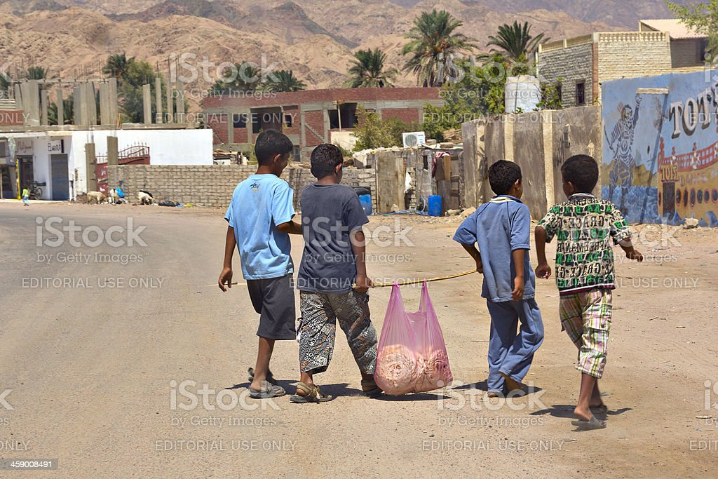 Egyptian children carry bag with bread stock photo