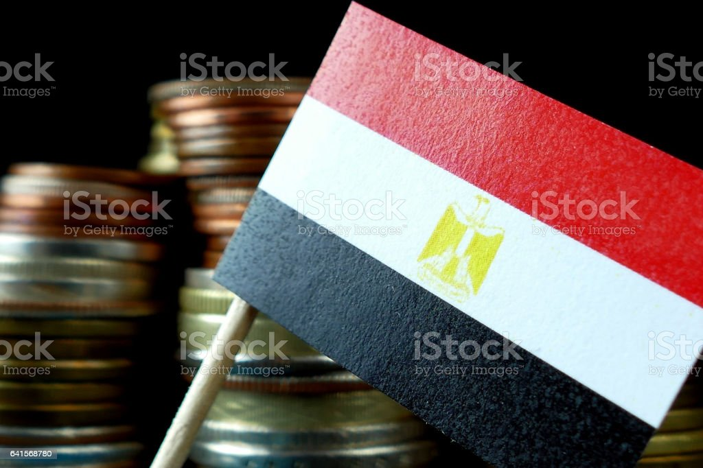 Egyptian flag waving with stack of money coins macro stock photo