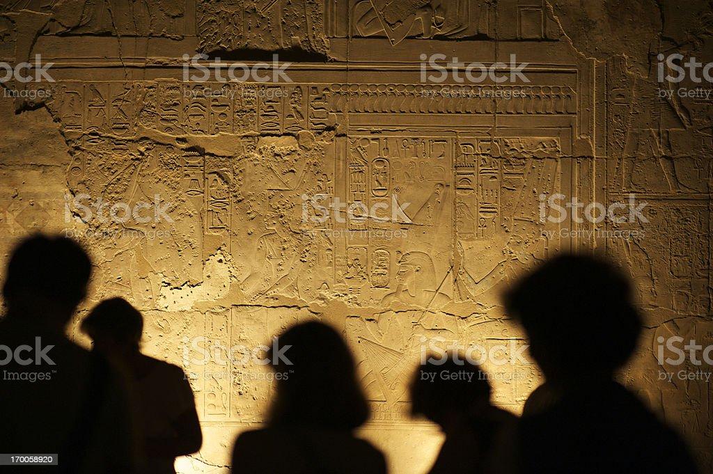 Egyptian Hieroglyphs with Tourist Silhouettes royalty-free stock photo