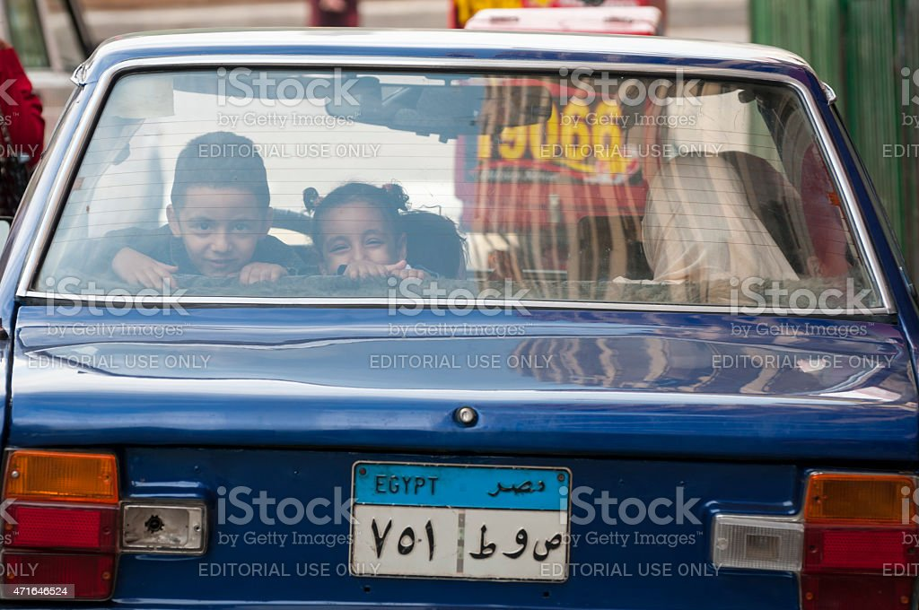 Egyptian kids in the back seat of a car in Cairo stock photo