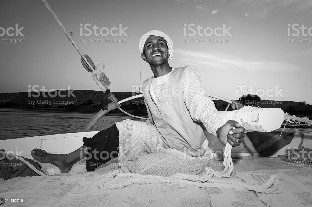 Egyptian man sailing a felucca on Nile River stock photo