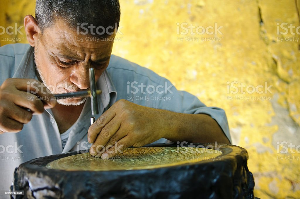 Egyptian metal worker doing his craft stock photo