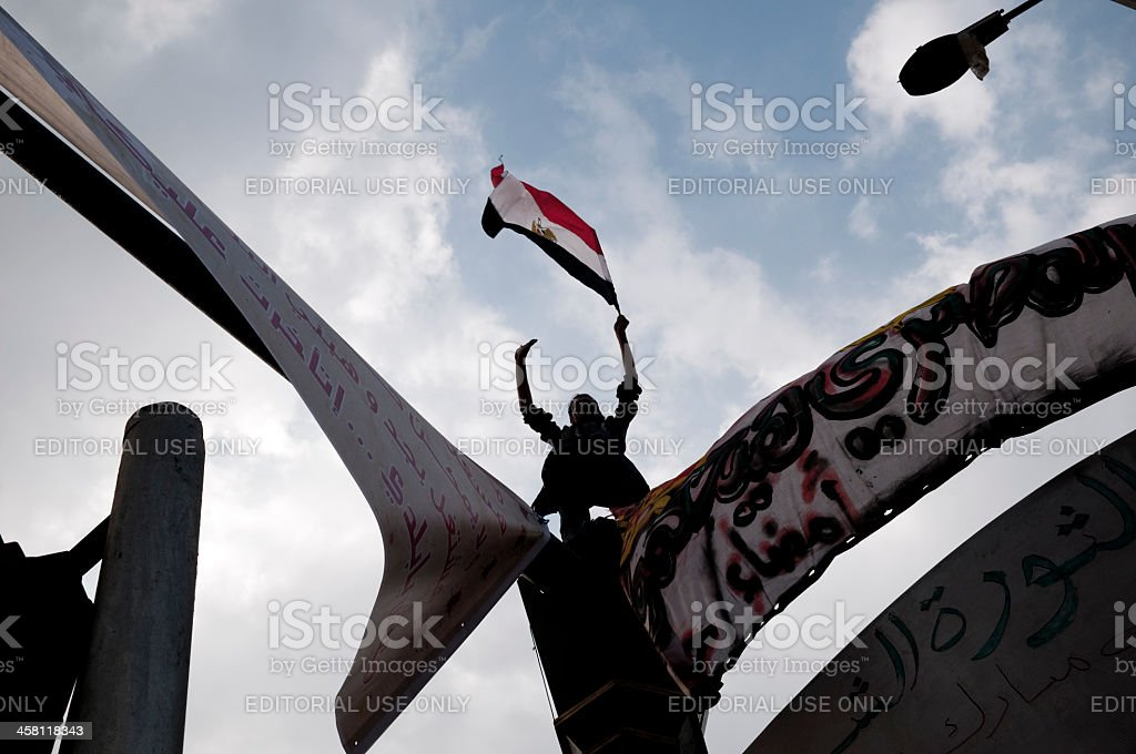 Egyptian revolution man with flag against sky stock photo