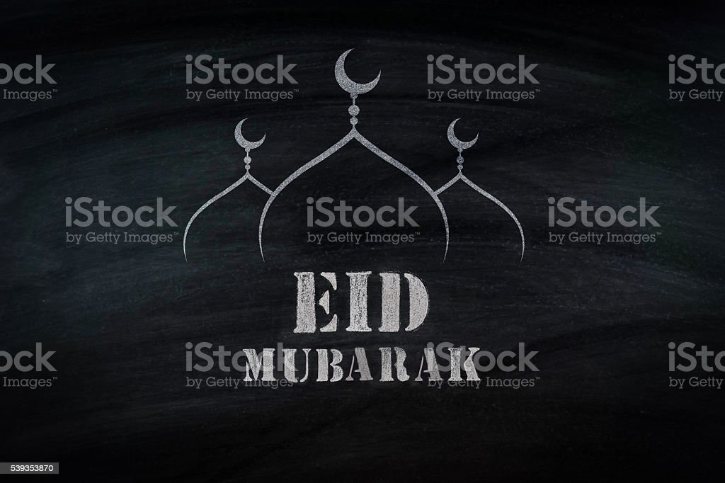Eid Mubarak, traditional Muslim greeting . On black broad stock photo