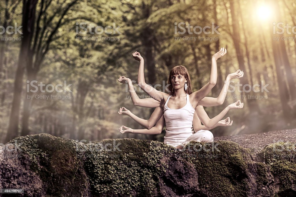 Eight arm woman sitting on a forest and pray stock photo