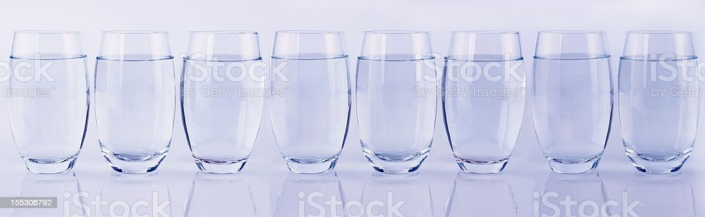 Eight glasses of water in a row stock photo