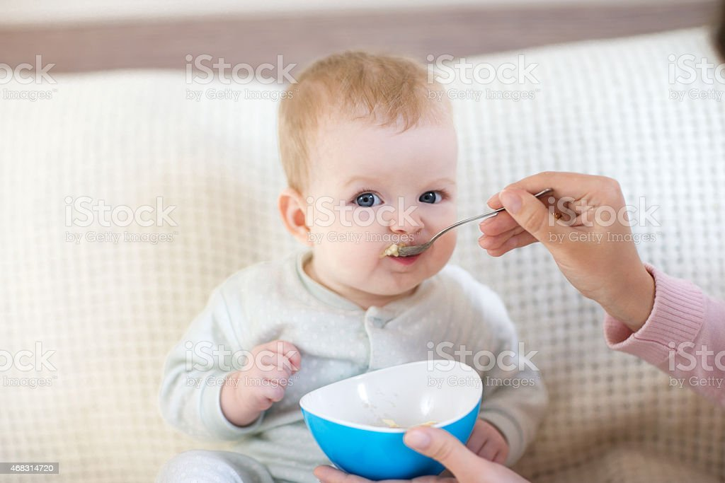 Eight month baby eating from the bowl stock photo