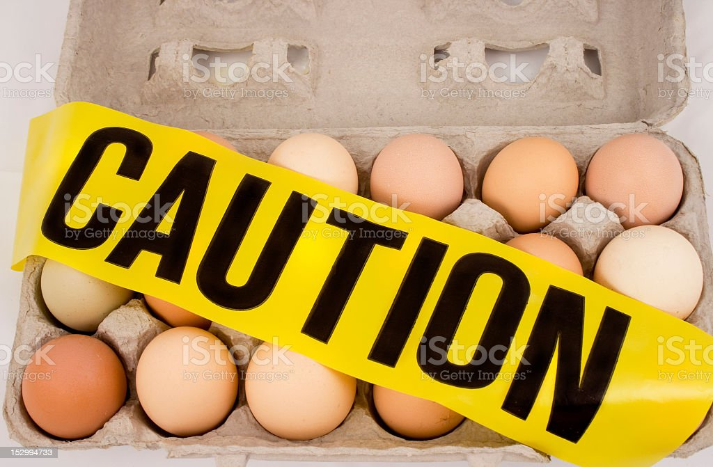 Eighteen eggs on a box with a caution sign over stock photo