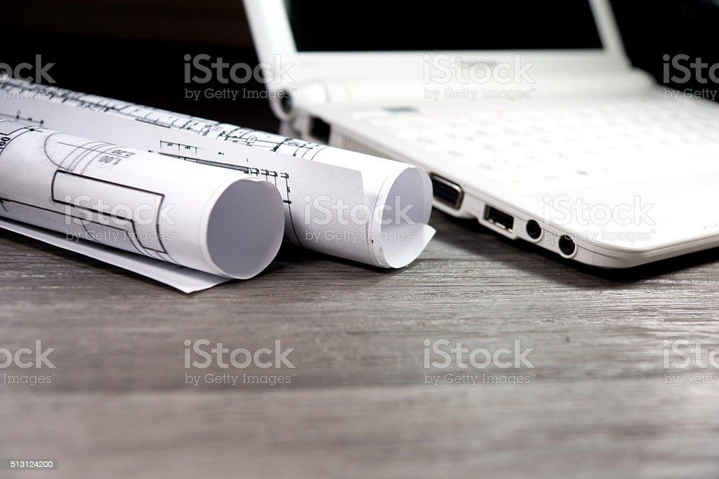 Ein Laptop und Baupläne stock photo