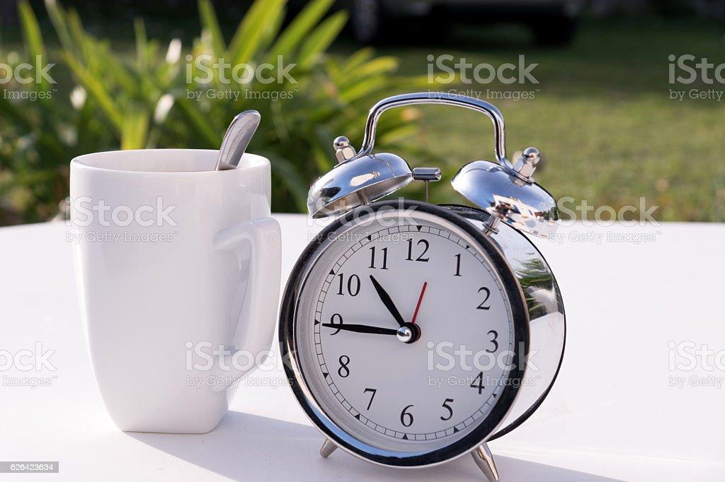 Ein Wecker auf dem Gartentisch stock photo