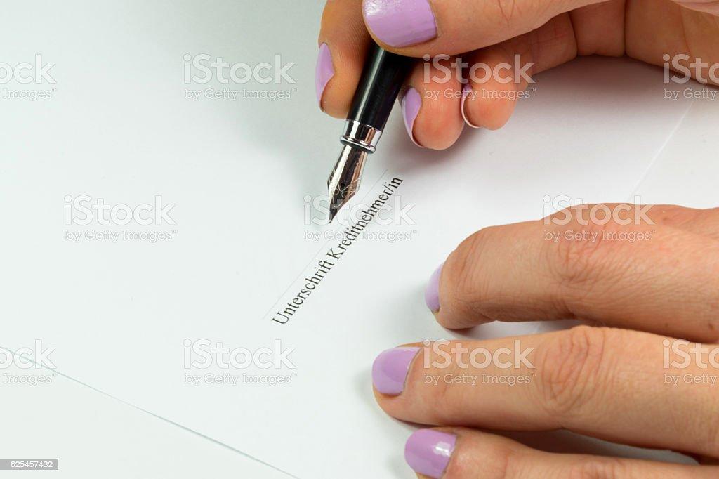 Eine Frau unterschreibt einen Kreditvertrag stock photo