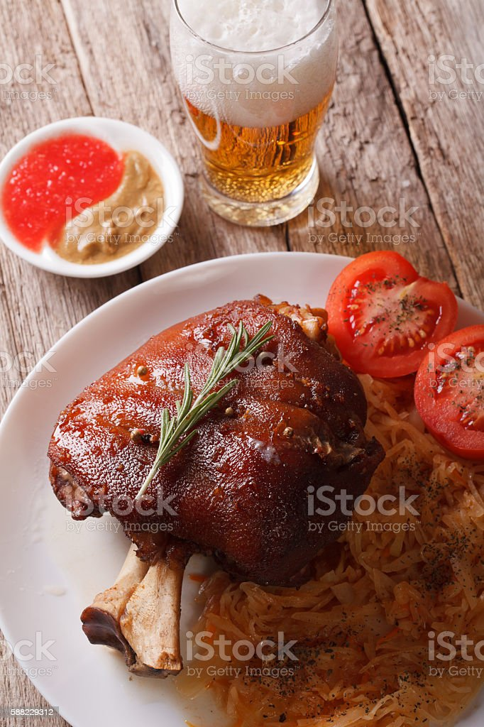 eisbein: baked pork shank and cabbage closeup and beer. vertical stock photo