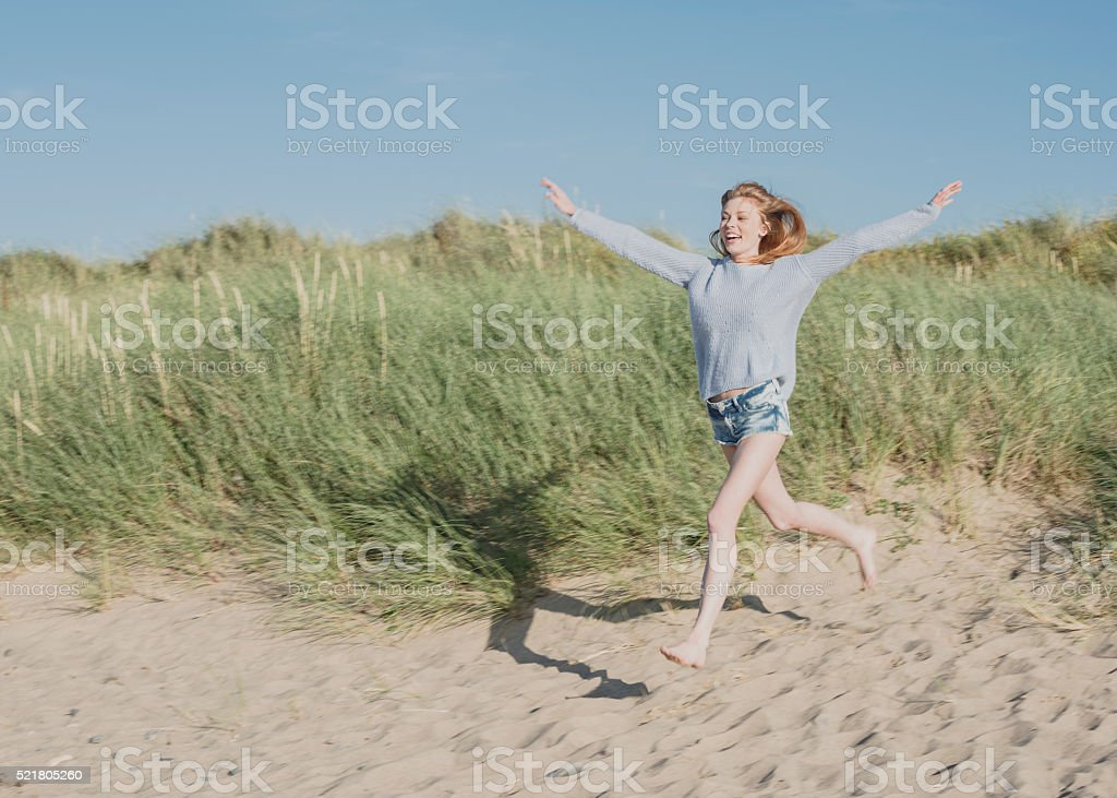Elated young woman running onto sandy beach stock photo