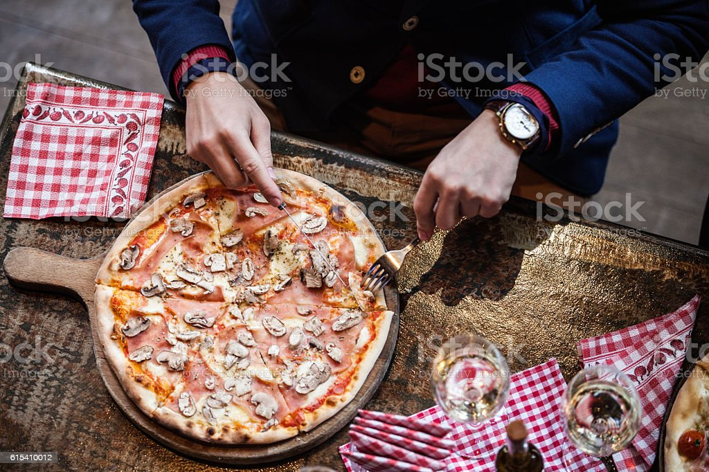 Elavated view of man eating pizza stock photo