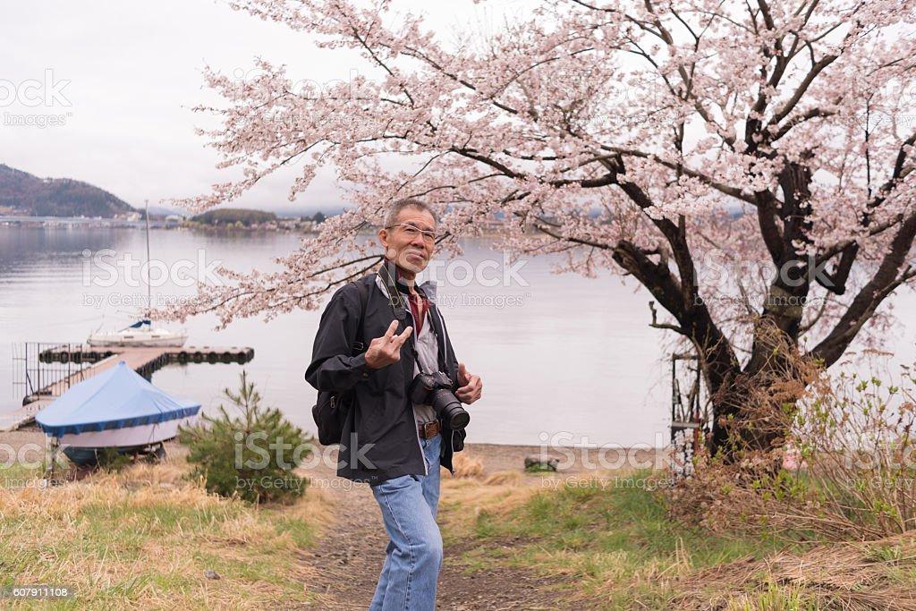 Elder asian man with camera on his neck with sakura. stock photo