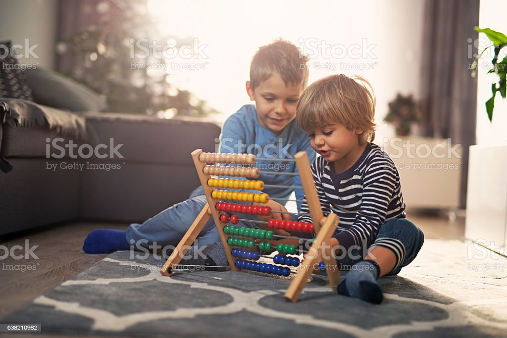 Elder brother helping little boy to count on abacus stock photo